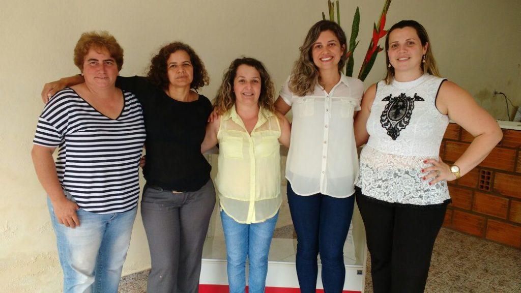 Cinco mulheres da diretoria executiva da AMPIC, em pé e abraçadas.