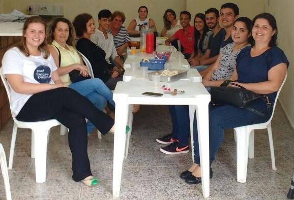Membros da AMPIC sentados em volta de uma mesa durante reunião.