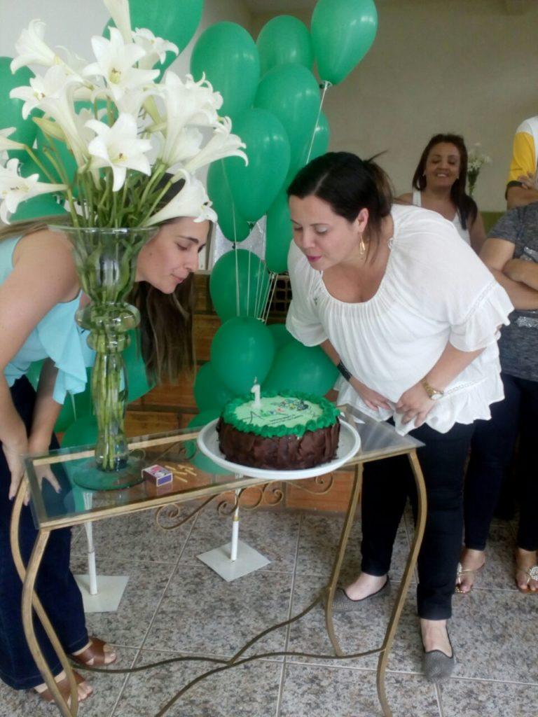 Presidenta Fernanda Guedes e vice-presidenta Larissa Tomaz soprando a velinha do 1º aniversário da AMPIC. Velinhas em um bolo numa mesa decorada com balões.